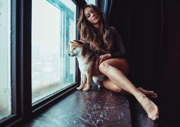 Young woman sitting with dog on window