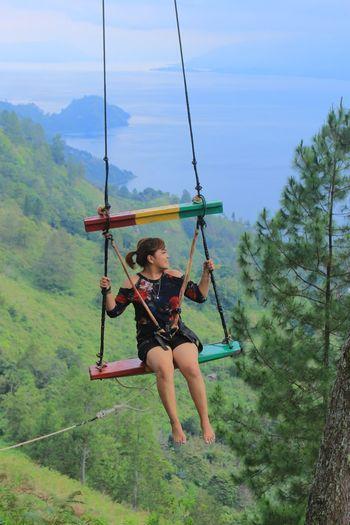 Full length of man holding swing hanging on rope
