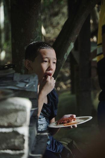 Boy eating food outdoors at night