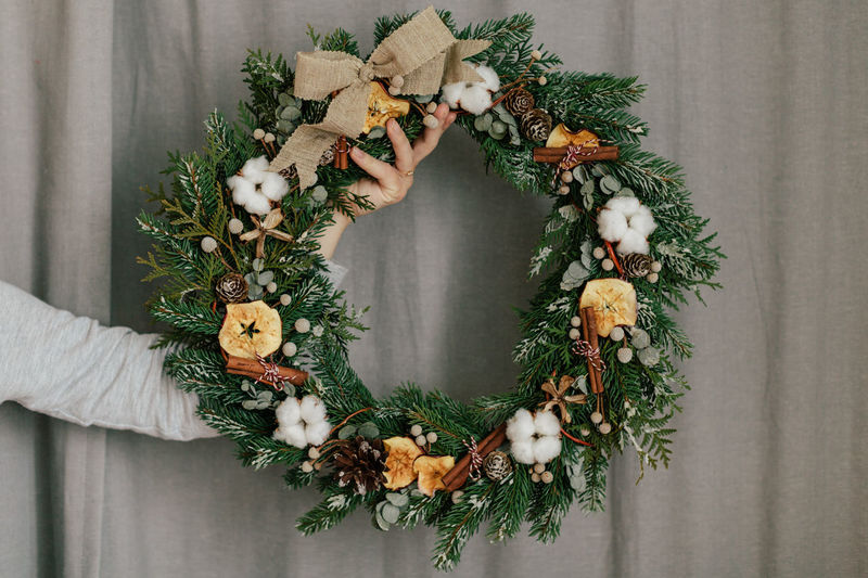 Cropped Hand Holding Wreath Against Curtain