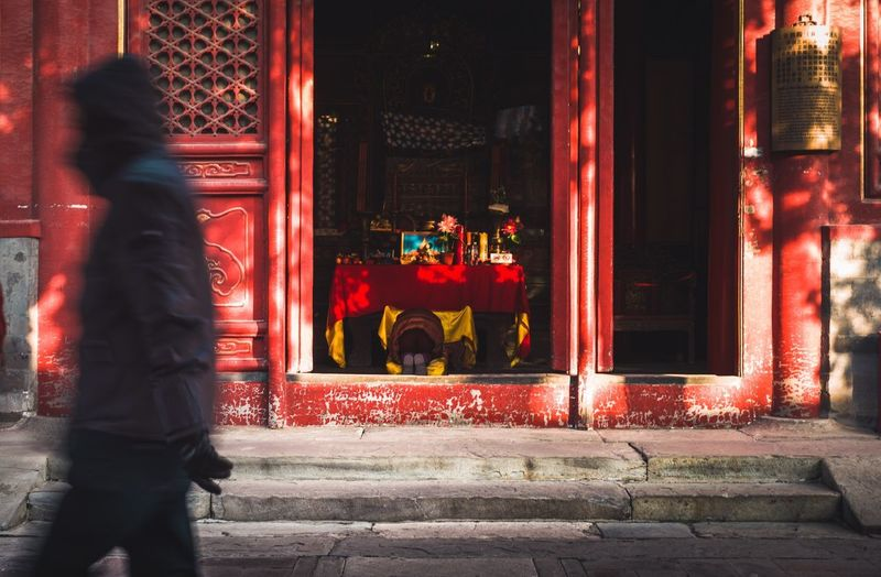 Man standing in red illuminated building at night