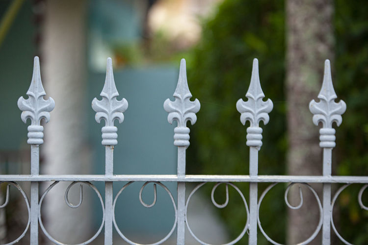 Close-up of metal gate against fence