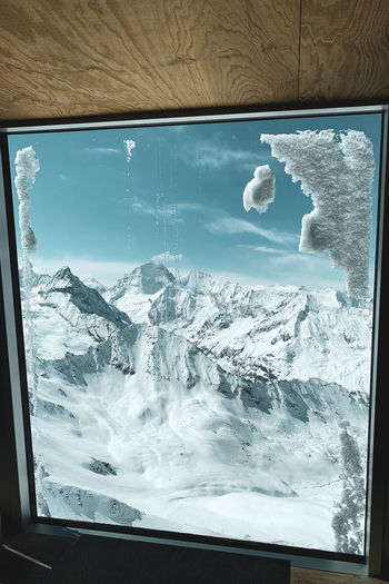 Scenic view of snowcapped mountains seen through glass window