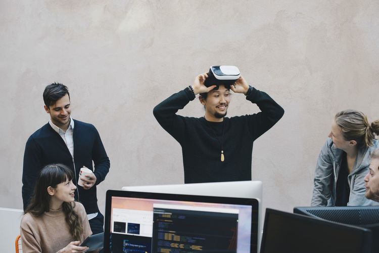 Male computer programmer wearing vr glasses while looking at colleagues in office