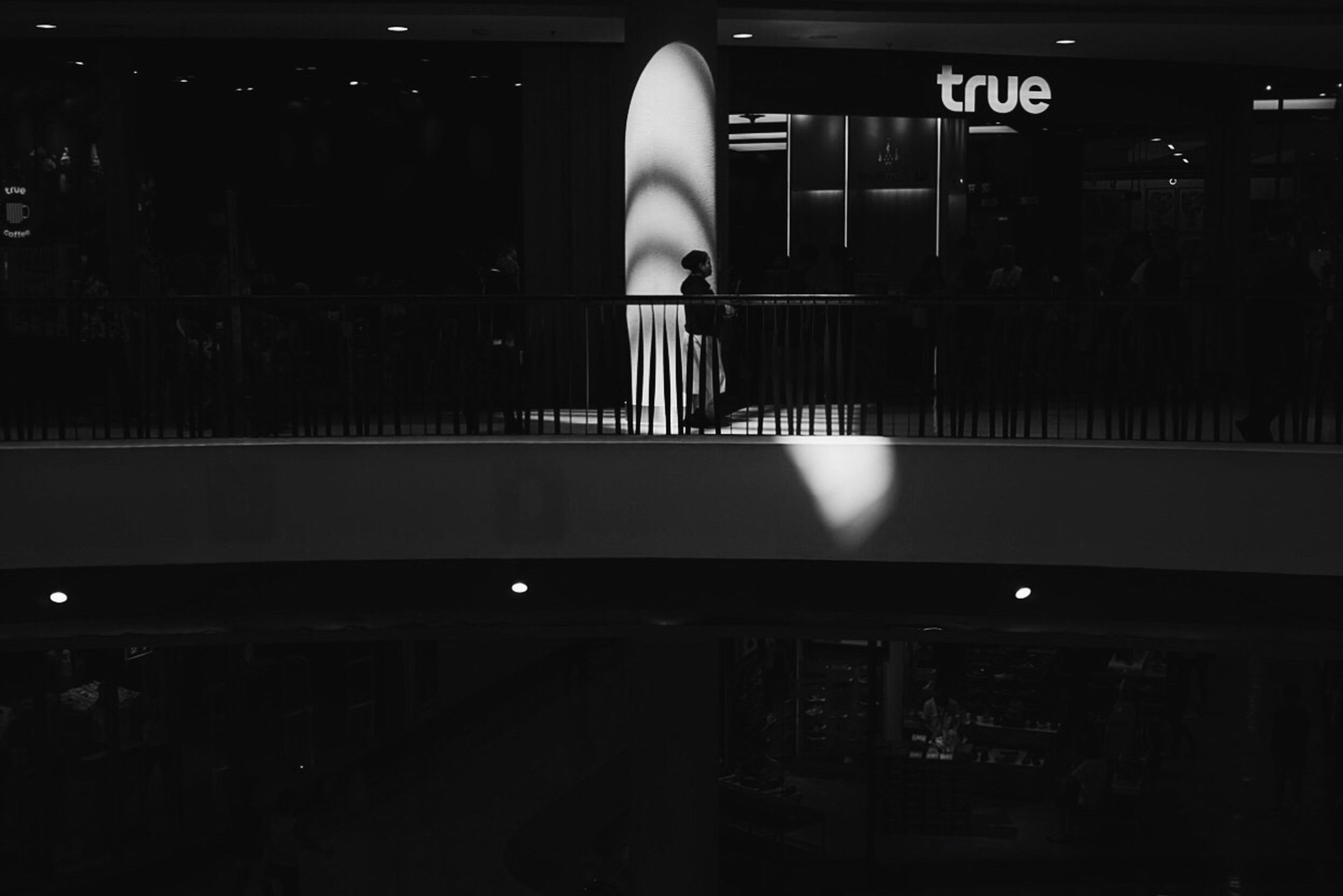 indoors, men, lifestyles, person, illuminated, leisure activity, rear view, standing, silhouette, communication, night, walking, public transportation, text, full length, unrecognizable person, waiting