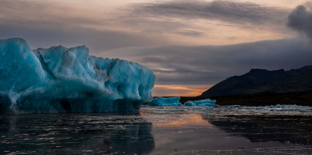 View of iceberg in sea during sunset