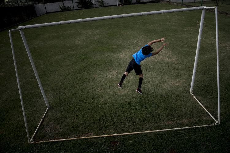 Full length of man playing soccer ball
