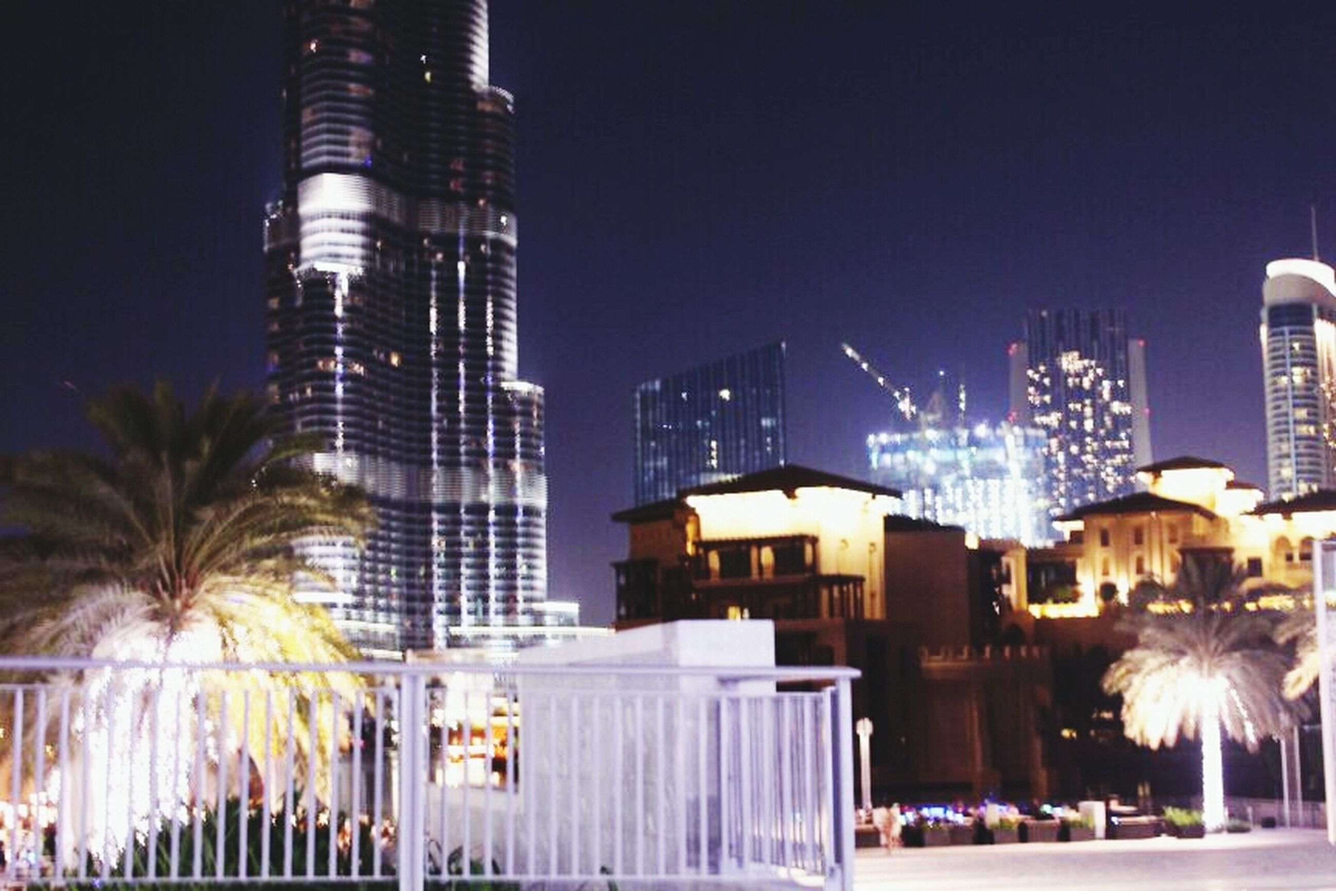 building exterior, architecture, built structure, illuminated, city, night, modern, skyscraper, clear sky, building, residential building, tall - high, office building, residential structure, cityscape, tower, blue, lighting equipment, low angle view, city life