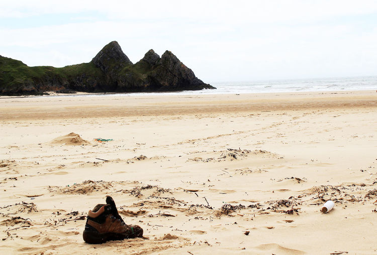 Lost sole Cliffs Three Cliffs Bay Beach Beachphotography Nature Outdoors Sand Sea Walking Boot An Eye For Travel
