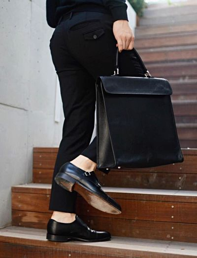 Low section of businessman carrying bag while climbing steps in office