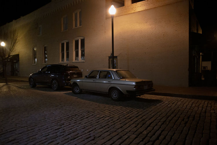 Car on street against illuminated buildings in city at night