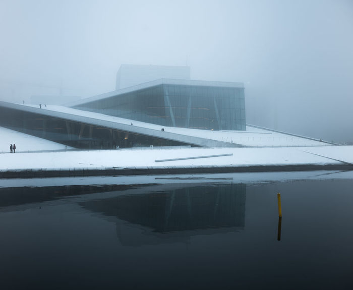 Snow-clad Oslo Opera House in mist. EyeEmNewHere Architecture Reflection Water No People Winter Waterfront Outdoors Snow Building Exterior Fog Oslo Opera House Blue Oslo