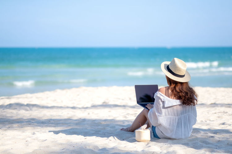A woman using and typing on laptop computer keyboard while sitting on a beautiful beach Space Sky Sitting Shoulder Sea Screen Sand Relax People Over Online  Notebook Nature Message Look Lifestyle Leisure Laptop Internet Holiday Holding Hand Girl Female Empty Display Device Desktop Copyspace Copy Connection Computer Communication Coconut Blue Black Beautiful Beach Background