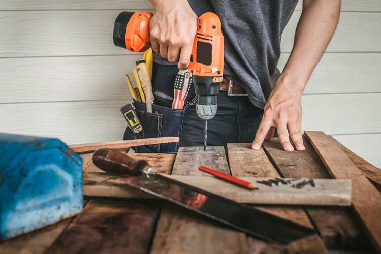 Midsection Of Carpenter While Using Drill Machine On Wooden Table