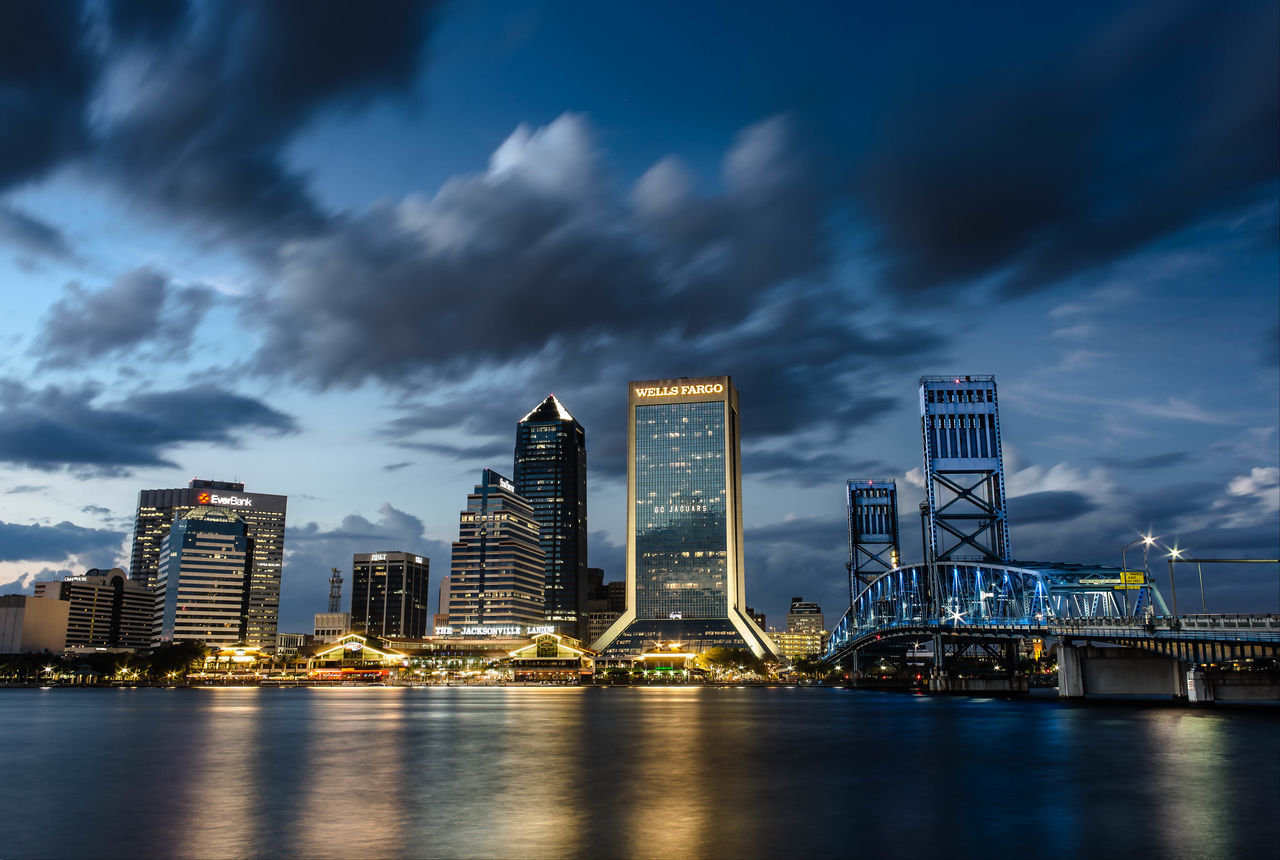 architecture, skyscraper, built structure, sky, cloud - sky, building exterior, waterfront, no people, city, travel destinations, water, cityscape, modern, urban skyline, outdoors, illuminated, sea, day, nature