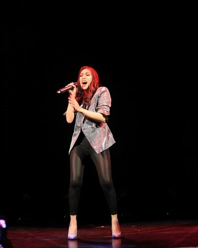 Woman singing on stage at night