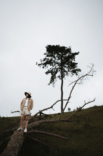 Full length of woman standing on tree trunk against sky