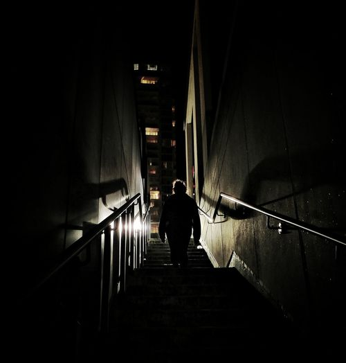 Rear view of silhouette man walking on staircase at night