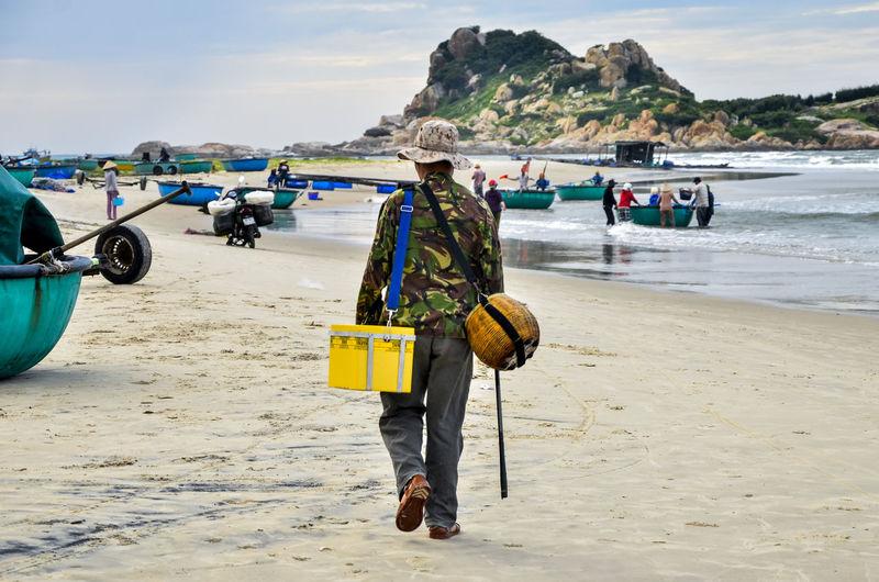 Rear view of fisherman walking on beach against sky