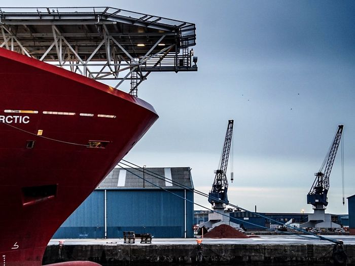 Cropped image of ship moored at commercial dock against sky