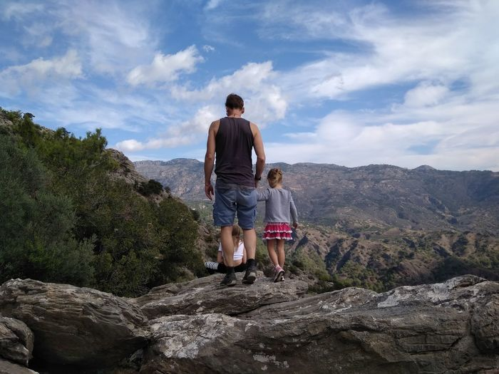 Rear view of man with daughters on cliff against cloudy sky
