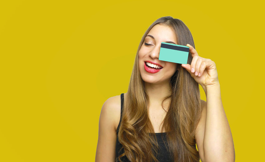 Happy young woman holding credit card against yellow background