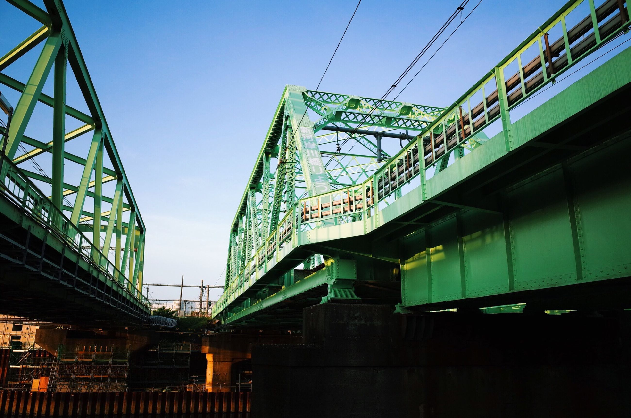 architecture, built structure, low angle view, connection, bridge - man made structure, building exterior, transportation, clear sky, rail transportation, engineering, railroad track, sky, city, cable, public transportation, power line, railroad station, metal, outdoors, train - vehicle