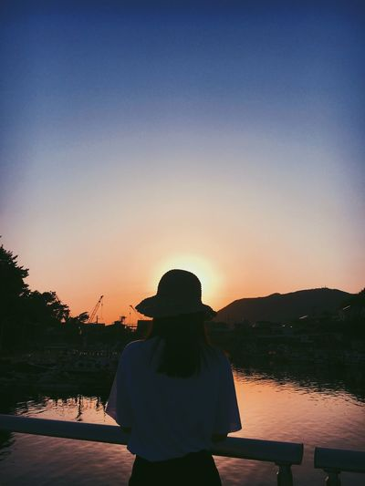 Rear view of woman looking at lake against sky during sunset