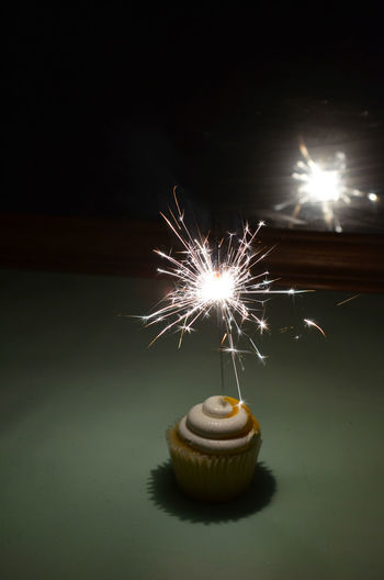 Close-up of sparkler on cupcake at table