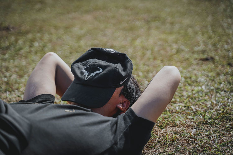 One Person Real People Land Lifestyles Leisure Activity Field Day Men Clothing Nature Plant Casual Clothing Rear View Relaxation Grass Black Color Focus On Foreground Lying Down Activity Outdoors Photographer Obscured Face