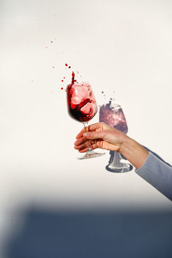 Person holding a glass of red wine