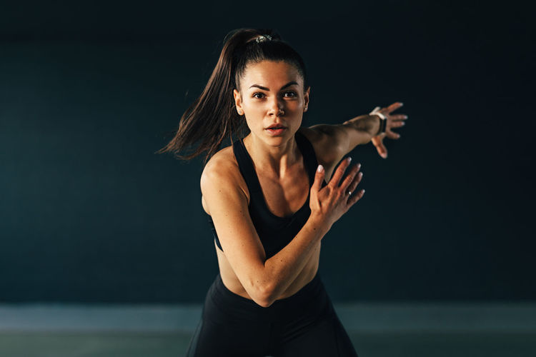 Portrait of young woman exercising against black background