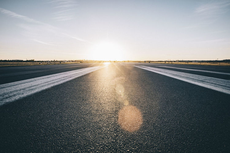 Airport Airport Runway Asphalt Direction Dividing Line Highway Horizon Over Land Lens Flare Marking Nature No People Outdoors Road Road Marking Sign Sky Sun Sunlight Sunset Symbol Transportation Travel