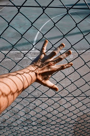 Hand with shadow shapes grabbing a metallic fence