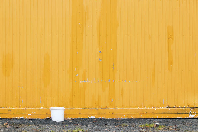 Foreground Foreground Focus Container Bucketlist Still Life Photography Wall Building Wall Congregated Steel Mellow Yellow Standing Bucket Still Life White Bucket Yellow Wall Worn Out Parking Garage Shed Corrugated Drum - Container