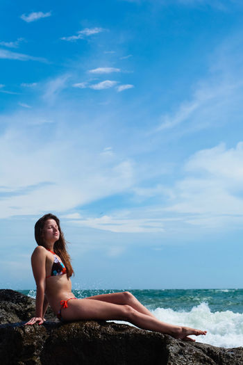 Woman Wearing Bikini While Sitting At Beach Against Blue Sky
