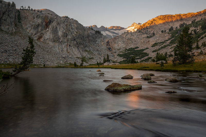 Hope it was unsweetened | JMT DAY 2 - SUNRISE AT LAKE BELOW DONOHUE PASS First lake below Donohue Pass to Island Pass: JMT201802001 Morning arrived at Donohue Pass and Mt. Lyell. It was a rather chilly one due to its elevation (about 10,180 feet). But then again, it was just one of many considerably-not-so-high lakes that we would hike to or camp at in the course of the following 30 days on the #JohnMuirTrail, or #JMT. Also, it marked the first morning for me to get up early, obviously way before sunrise, so that I could be ready. And it was still dark. The crisp and cold air embraced me as soon as I stepped out of my tent. Obviously though I had no idea that I was starting this getting-up-early, staying-up-late routine for the following 30 days. Yay me. The sunrise glow was cast on the tip of the peaks, including Mt. Lyell. And it was quite intense orange and beautiful. Such a bright and almost hypnotic glow. Can't get enough of it. And it was the reason why I got up that early! Did I mention that the mountain is the tallest peak (13,114 feet) in Yosemite National Park? Maybe I should consider day hiking it one day. I was delighted by the fact that the reflection of the glow in the water came through. As if somebody just stirred the large pouch of the Orange Kool Aid in it. Hope it was unsweetened. Soon, the glow faded. And it was time for me to return to my tent and get myself coffee. Donohue Pass, Yosemite National Park, CA Donohue Pass Lyell Fork Mt. Lyell Sunrise Silhouette Yosemite National Park Backcountry Beauty In Nature Flowing Flowing Water Idyllic John Muir Trail Lake Long Exposure Mountain Mountain Range Nature No People Non-urban Scene Remote Scenics - Nature Sunrise Tranquil Scene Tranquility Water Wilderness