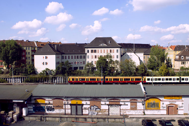 High Angle View Of Train Moving On Bridge By Buildings