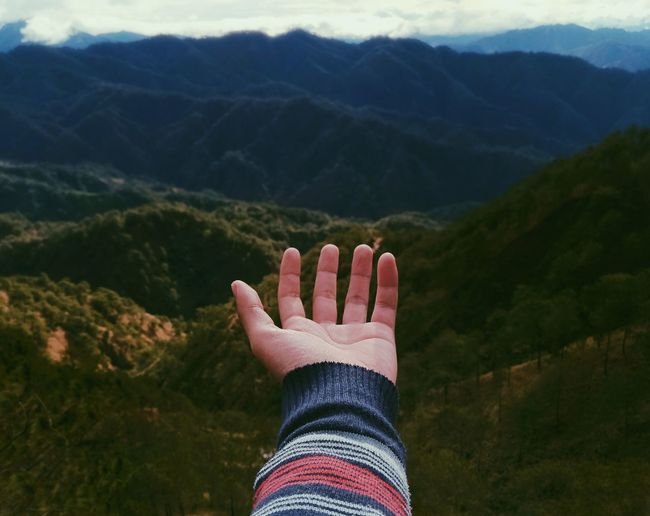 Cropped Hand Against Mountains