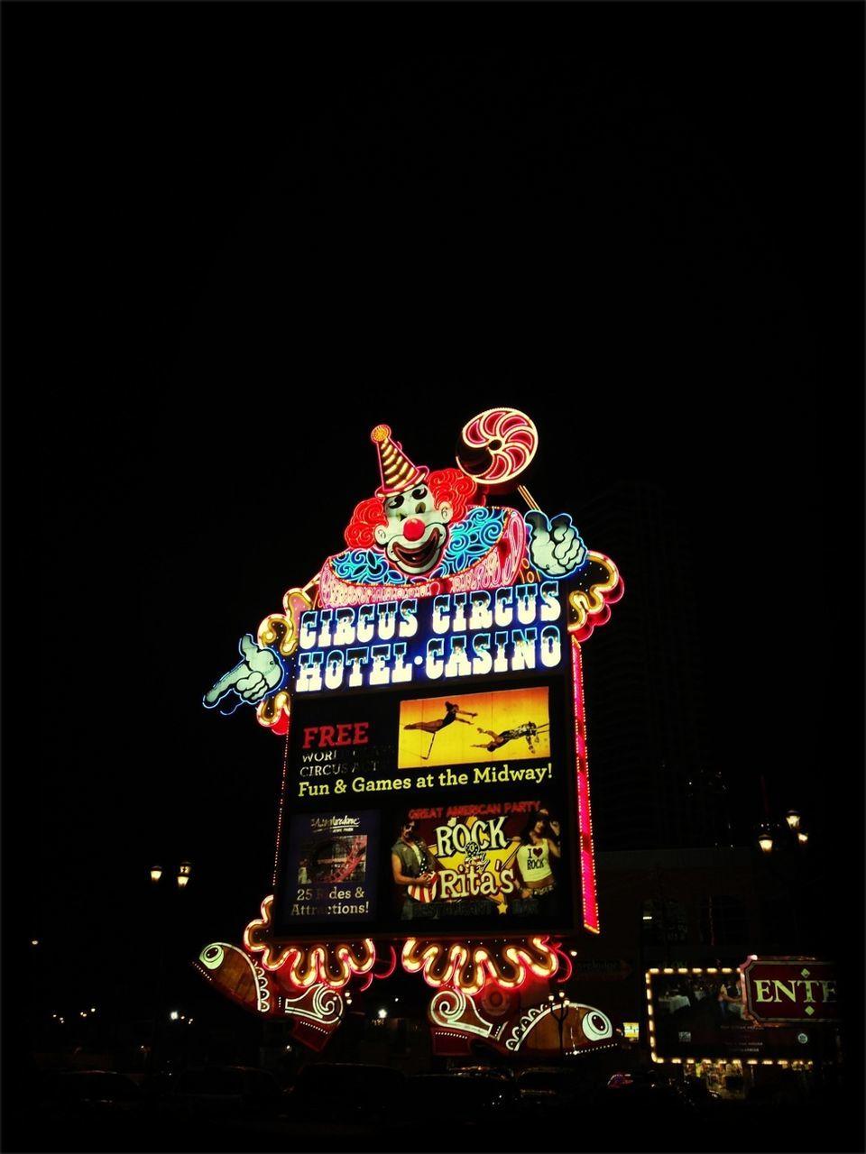 Illuminated circus circus casino sign against sky at night