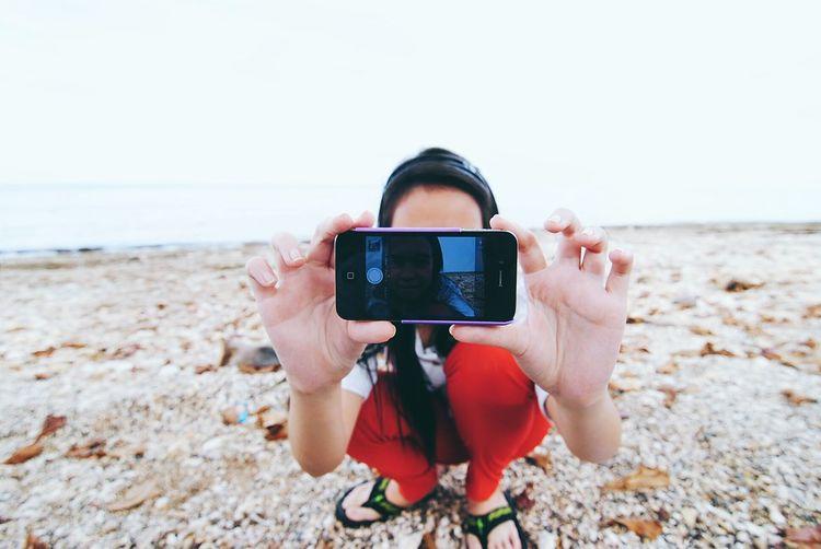 Photographer photographing on beach