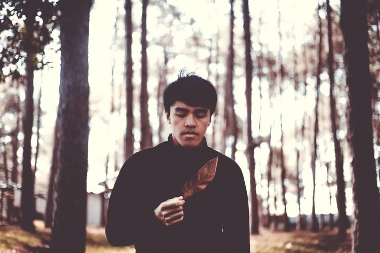 Young Man Holding Leaf While Standing In Forest