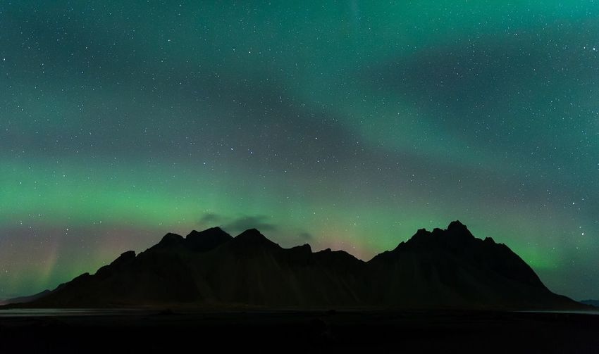 Scenic view of rocky mountains against aurora borealis in sky at night