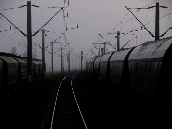 Railroad tracks by electricity pylon against sky