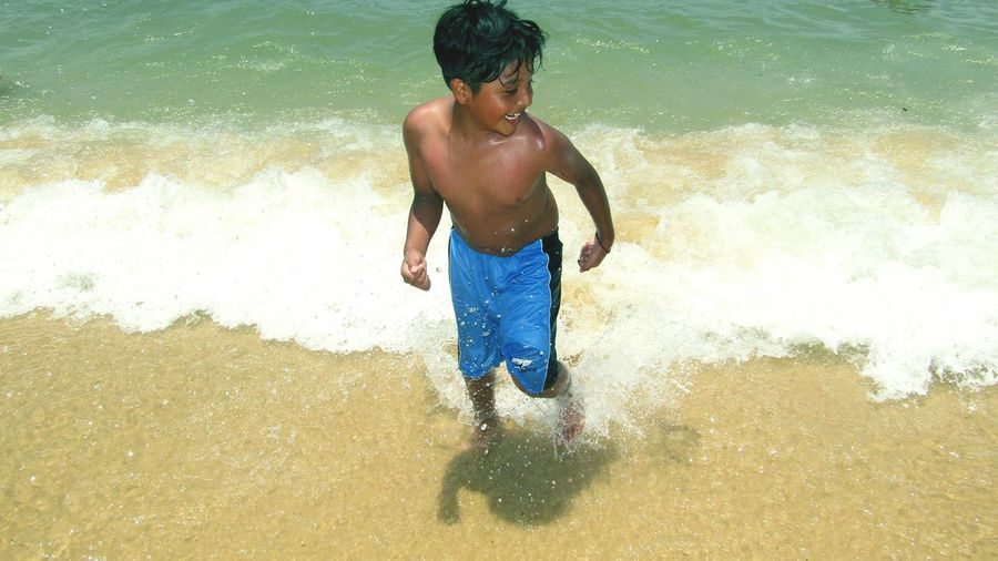 High angle view of shirtless boy enjoying on shore at beach