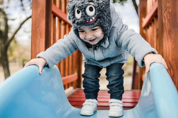Full length of cute baby boy standing on slide at playground