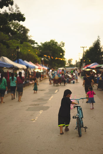 Boy And His Bike Playing Beautiful Day Luang Prabang, Laos Bicycle Blue Bicycle Boy Boy Has A Mullet Boy Wheeling Bicycle Boy's Mullet Laos Laos Street Laos Street Photo Laos Street Photography Laos Street Scene Laotian Streets Luang Prabang Luang Prabang Old Quarter Mullet Street Photography Street Scene Wheeling Bicycle