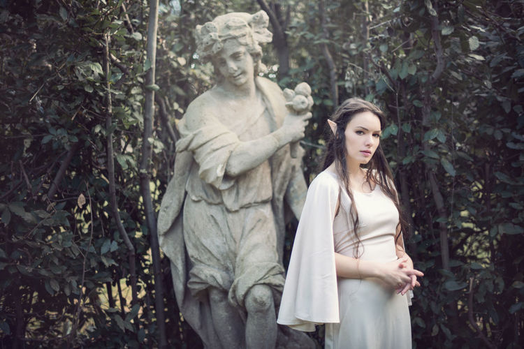 Young woman standing by statue in forest