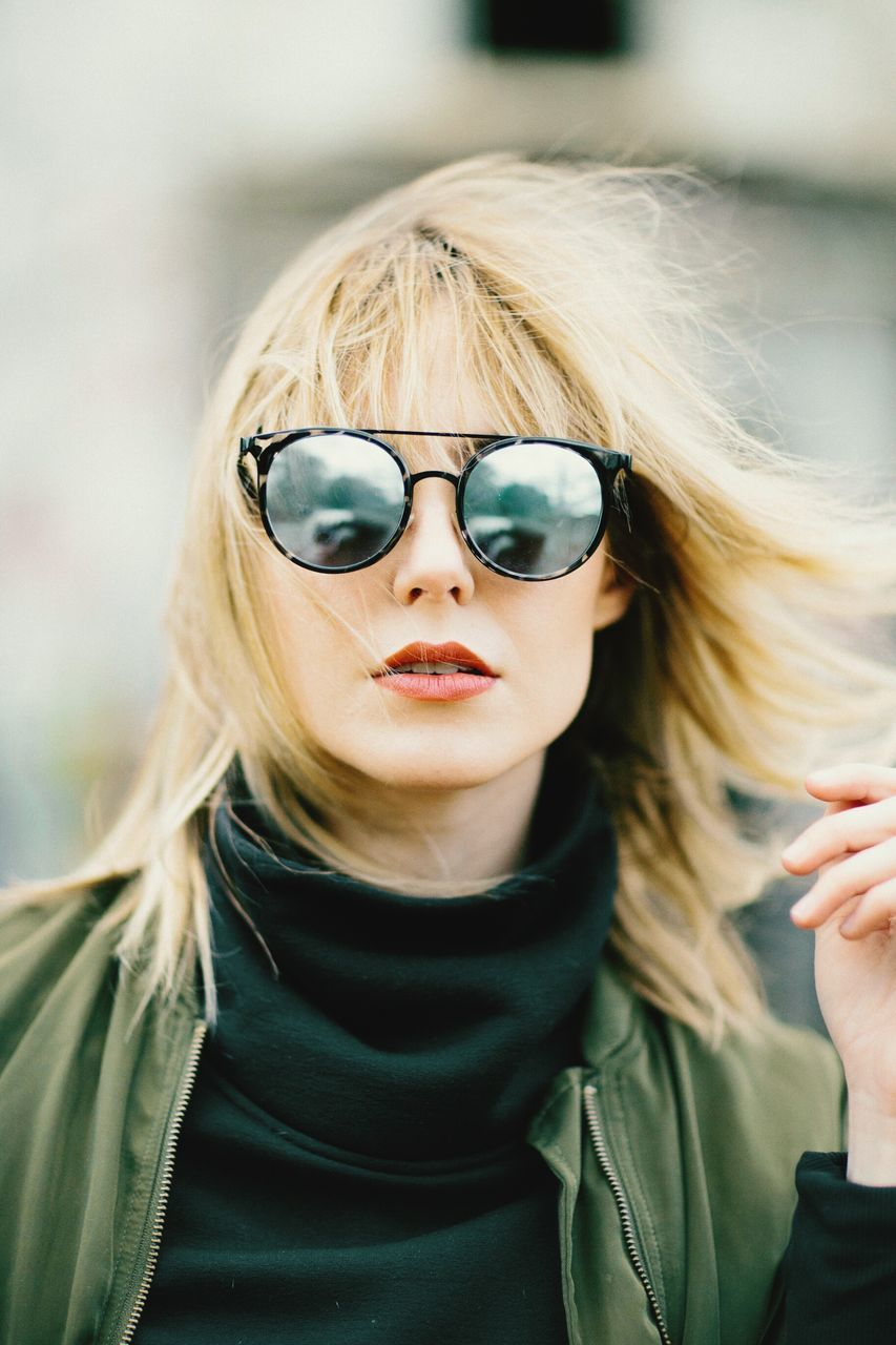 sunglasses, real people, blond hair, focus on foreground, front view, one person, lifestyles, fashion, eyeglasses, leisure activity, day, close-up, outdoors, young women, young adult, human hand