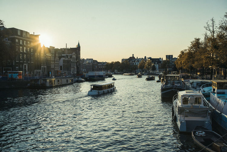 Boats moored in river against buildings in city at sunset